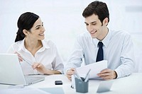 Professionals working together at desk, man holding document