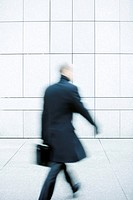 Businessman hurrying down sidewalk