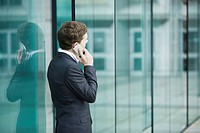 Young businessman standing outside sliding glass doors talking on cell phone