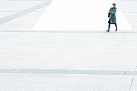 Woman with arms folded walking across city square