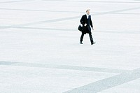 Businessman hurrying across public square