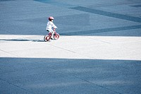 Child riding bicycle alone in public square
