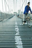 Man riding bike across pedestrian walkway of Brooklyn Bridge in New York City, Manhattan skyline in distance