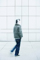 Man walking with hands in pockets on sidewalk (thumbnail)