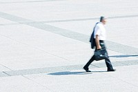 Businessman with jacket on shoulder walking across public square (thumbnail)