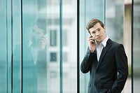 Businessman standing by glass wall talking on cell phone (thumbnail)