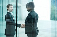 Businessman and businesswoman meet and shake hands at building entrance