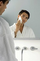 Man looking at himself in mirror, applying shaving cream