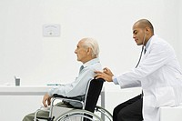 Elderly man sitting in wheelchair, doctor using stethoscope on back