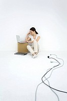Young woman sitting on the ground, using laptop computer, loose electric cords nearby
