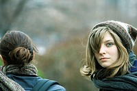 Young woman walking with friend in park, looking over shoulder at camera
