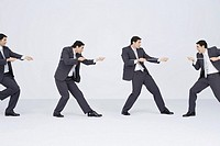 Businessman playing tug-of-war with clones of self, digital composite