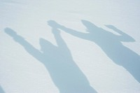 Shadow of people raising arms on snow