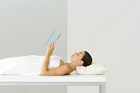 Woman wrapped in towel, lying on massage table, holding book, eyes closed