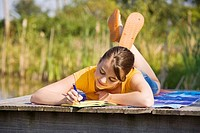 Teenaged girl lying on footbridge and writing in her diary with a slow smile