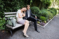 Couple sitting on bench in park, New York City