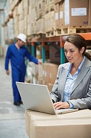 Businesswoman using laptop computer in warehouse