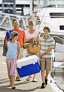 Family on boat dock with cooler and picnic basket