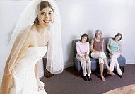 Bride trying on wedding dress with friends