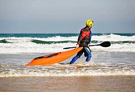 Canoeist sportman with a canoe in a beach, Berria beach, Santoña, Cantabria, Spain