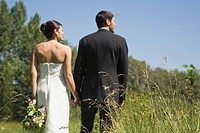 Bride and bridegroom walking through countryside