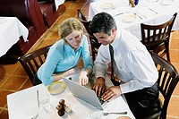 Businesspeople using laptop computer at restaurant