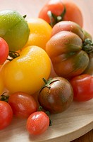Various types of tomatoes on wooden plate detail