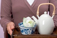 Woman holding tray of tea things teapot, tea bowl, flower