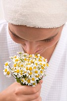 Woman smelling chamomile flowers (thumbnail)