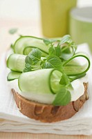 Yoghurt, cucumber slices and herbs on slice of bread