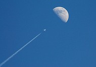 A passenger jet appears to fly directly toward the moon