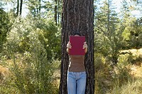 Woman holding books by tree
