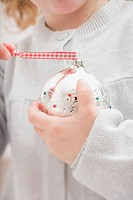 Small girl holding Christmas bauble