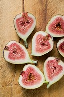 Several fig halves on wooden background