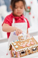 Small girl decorating gingerbread house with sugar