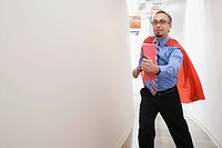 Businessman in cape running through hallway