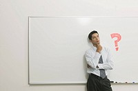Man thinking in front of white board