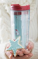 Woman holding star biscuit and insulated beaker