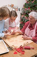 Grandmother showing grandchildren cut_out Christmas biscuit