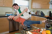 Mid_adult couple dancing in kitchen