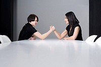 two young businesswomen doing arm wrestling at conference table