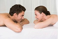 young couple lying on massage bench smiling at each other