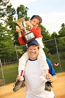 Young baseball player holding trophy while riding on coach´s shoulders