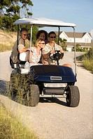 Couples riding together in golf cart