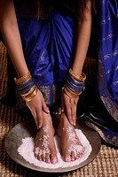Indian woman with feet in salt scrub