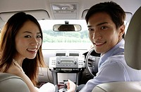 Couple driving in car, looking in back seat