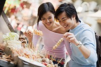 Couple Choosing Skewers of Food