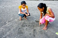 Village girls practising sums in beach sand, Puerto Barrios, Guatemala