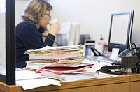 Stack of Paperwork on Businesswoman´s Desk