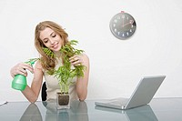 A businesswoman watering a plant